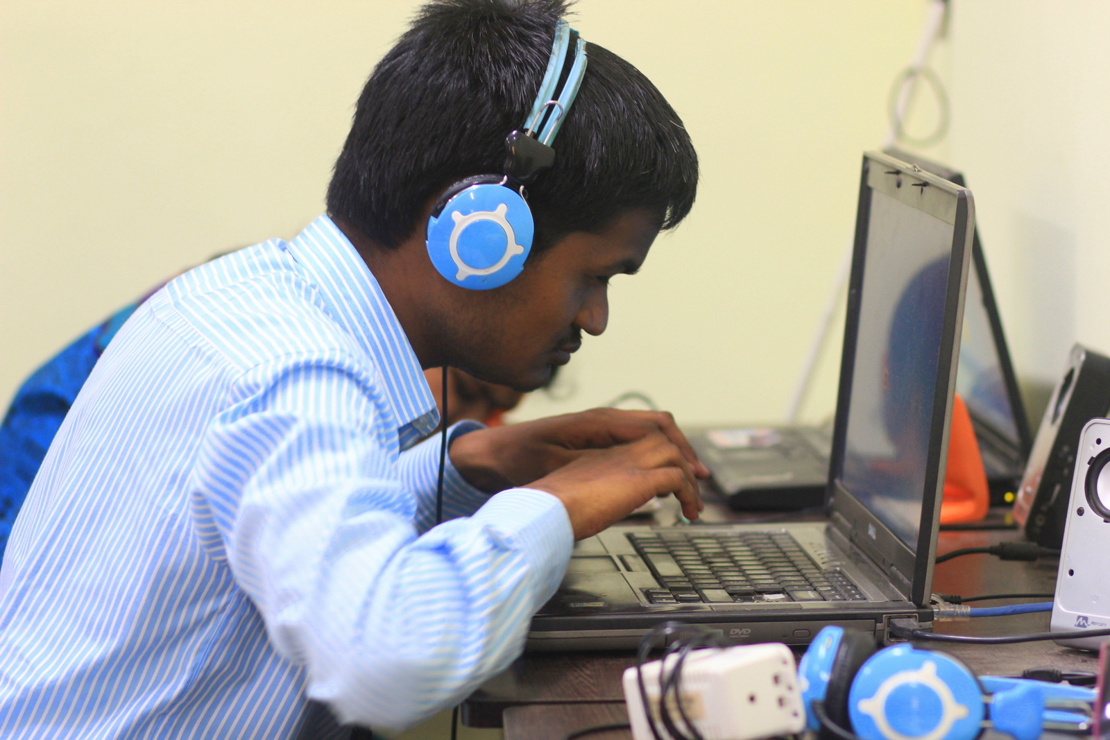 Person with vision impairment using laptop with headset