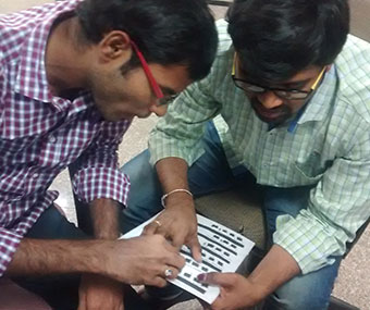 Trainer teaching a visually impaired participant desktop layout using tactile diagram