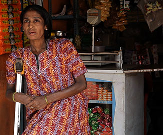 Woman with crutches standing in front of kirana shop